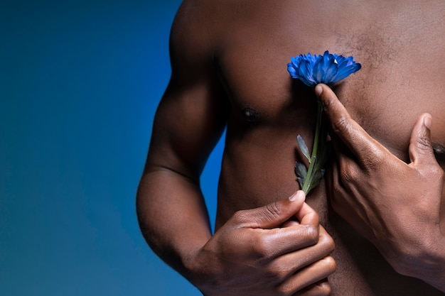 African american man holding a blue flower