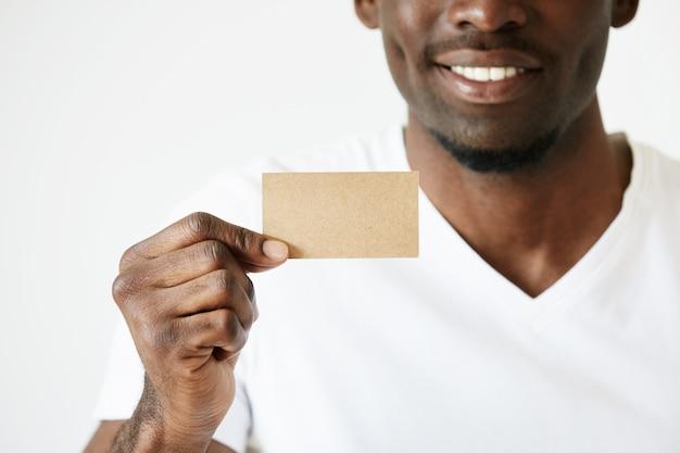 Афро-американский мужчина держит коричневую пустую визитную карточку