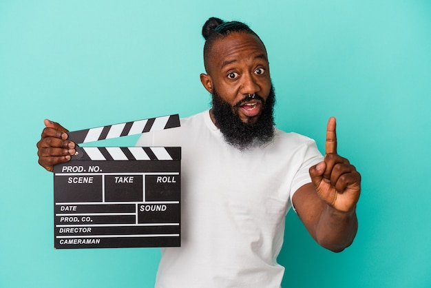 African american man holding clapperboard isolated on blue background having an idea, inspiration concept.