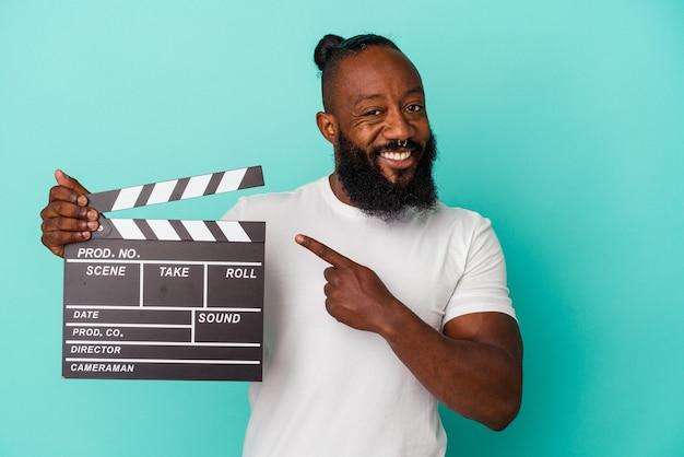青い背景に分離されたカチンコを持っているアフリカ系アメリカ人の男が笑顔で脇を指して、空白のスペースで何かを示しています。