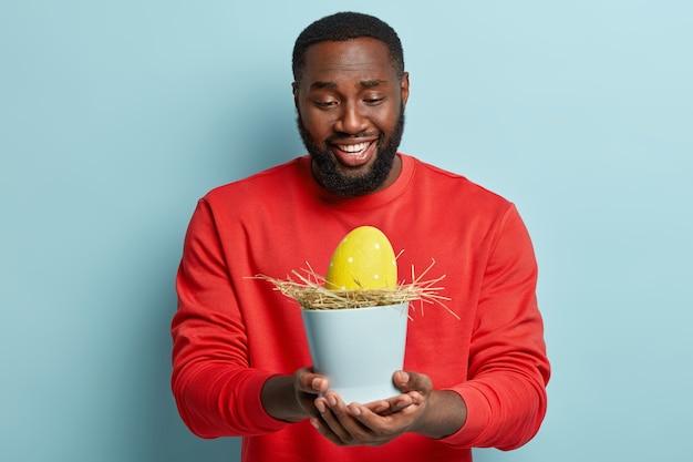 イースターエッグを保持しているアフリカ系アメリカ人の男