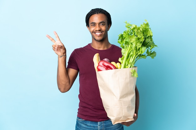 African american man holding a grocery shopping bag on blue smiling and showing victory sign