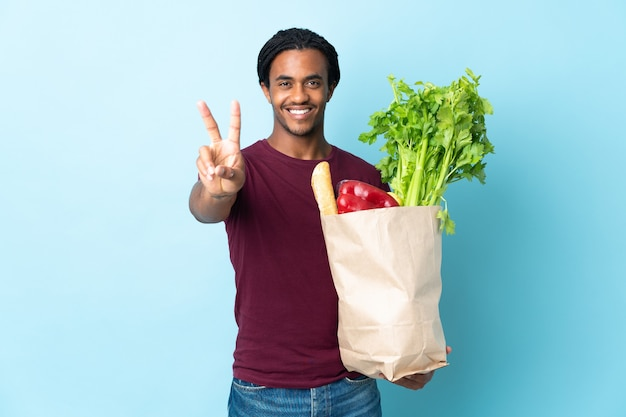 African american man holding a grocery shopping bag isolated on blue wall smiling and showing victory sign