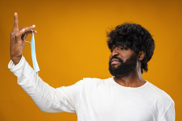 Афро-американский мужчина с отвращением держит медицинскую маску на желтой поверхности
