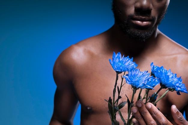 いくつかの花を持っているアフリカ系アメリカ人の男