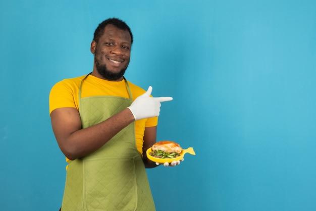 Uomo afroamericano che tiene con il pasto sopra la parete blu-chiaro che indica felice con la mano ed il dito.