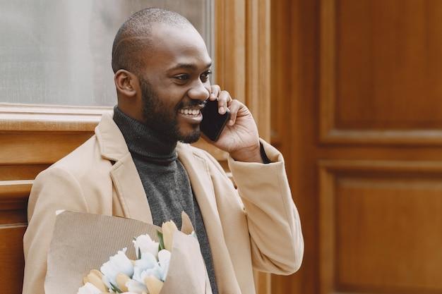 都市のアフリカ系アメリカ人の男。花の花束を持っている男。茶色のコートを着た男性。