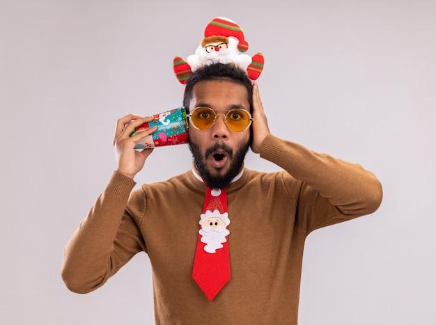 갈색 스웨터와 흰색 배경 위에 서 깜짝 놀라게 그의 귀에 다채로운 종이 컵을 들고 머리에 산타 테두리에 아프리카 계 미국인 남자