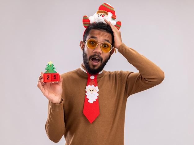 카메라에 날짜 25 loking 장난감 큐브를 들고 재미 빨간 넥타이와 머리에 갈색 스웨터와 산타 테두리에 아프리카 계 미국인 남자는 흰색 배경 위에 서 놀란