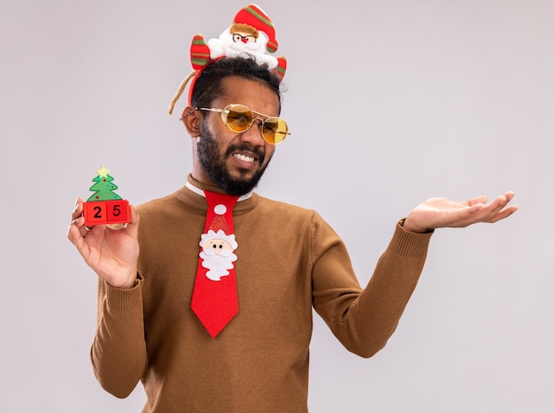갈색 스웨터와 산타 테두리에 재미 있은 빨간 넥타이로 머리에 아프리카 계 미국인 남자 25 날짜와 장난감 큐브를 들고 흰색 배경 위에 서 팔으로 불쾌 하 게 카메라를보고