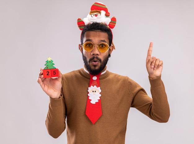 재미 있은 빨간 넥타이로 머리에 갈색 스웨터와 산타 테두리에 아프리카 계 미국인 남자 25 날짜와 장난감 큐브를 들고 카메라를보고 놀란 된 보여주는 검지 손가락 흰색 배경 위에 서