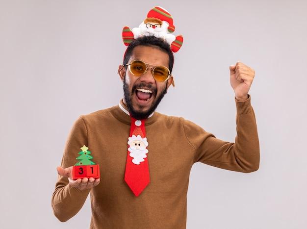 갈색 스웨터와 흰색 배경 위에 서있는 카메라 행복하고 흥분 떨림 주먹을 떨리는 새 해 날짜와 장난감 큐브를 들고 재미있는 빨간 넥타이와 머리에 산타 테두리에 아프리카 계 미국인 남자