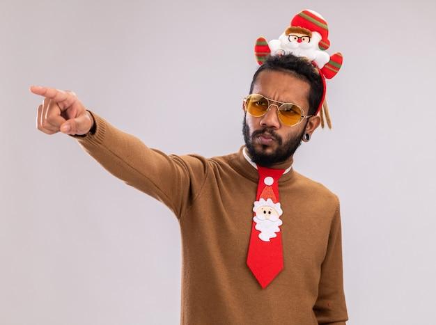 Афро-американский мужчина в коричневом свитере и ободке санта-клауса на голове с забавным красным галстуком смотрит в сторону с серьезным лицом, указывая указательным пальцем на что-то стоящее на белом фоне