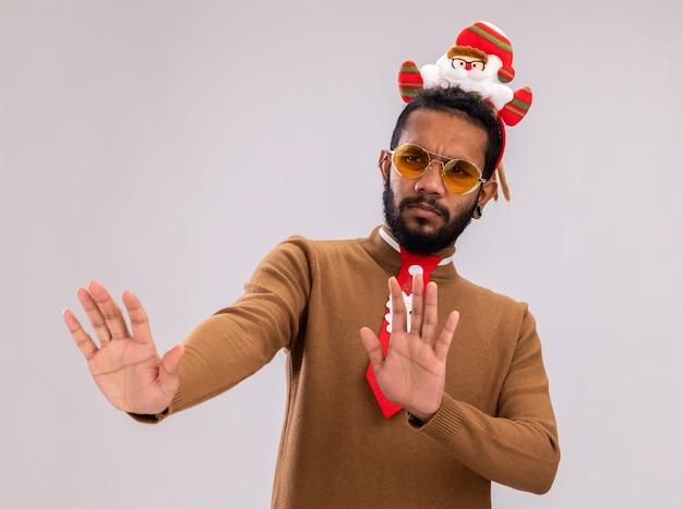 갈색 스웨터와 재미있는 빨간 넥타이와 머리에 산타 테두리에 아프리카 계 미국인 남자 옆으로 찾고 방어 제스처 서 흰색 배경 위에 서 걱정