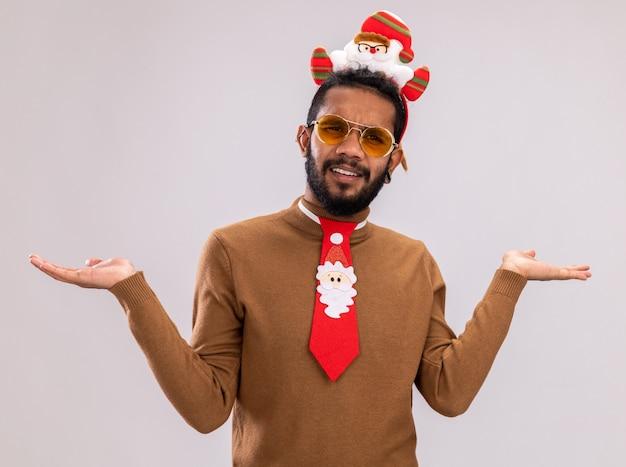 갈색 스웨터와 산타 테두리에 아프리카 계 미국인 남자 카메라를보고 재미 빨간 넥타이와 머리에 혼란과 흰색 배경 위에 서 불쾌