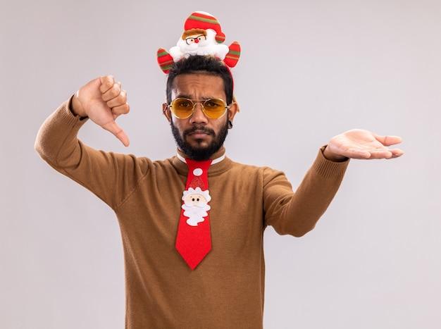 Афро-американский мужчина в коричневом свитере и ободке санта-клауса на голове с забавным красным галстуком смотрит в камеру, показывает палец вниз, представляет руку, стоящую на белом фоне