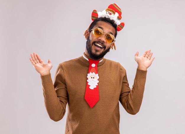 갈색 스웨터와 흰색 배경 위에 유쾌 하 게 서 웃 고 카메라를보고 재미있는 빨간 넥타이와 머리에 산타 테두리에 아프리카 계 미국인 남자