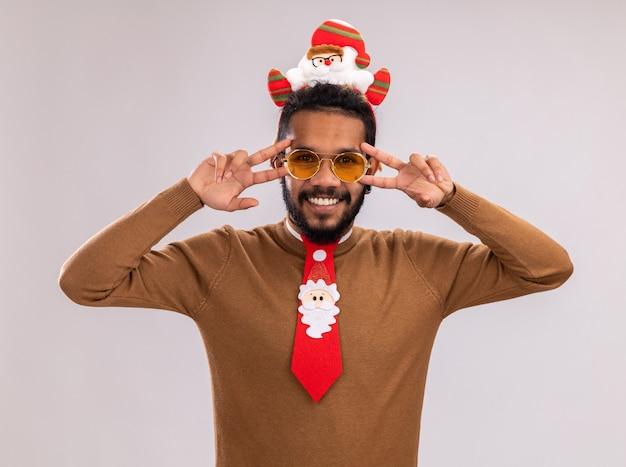 갈색 스웨터와 흰색 배경 위에 서있는 눈 근처 v 기호를 보여주는 얼굴에 미소로 카메라를보고 재미 빨간 넥타이와 머리에 산타 테두리에 아프리카 계 미국인 남자