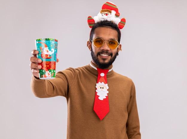 Афро-американский мужчина в коричневом свитере и ободке санта-клауса на голове с забавным красным галстуком показывает красочный бумажный стаканчик, глядя в камеру, весело улыбаясь, стоя на белом фоне