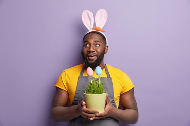イースターエッグを保持しているウサギの耳にアフリカ系アメリカ人の男