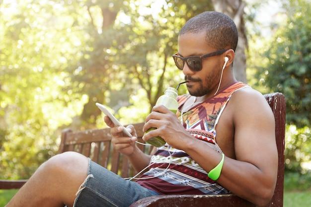Афро-американский мужчина в наушниках сидит на скамейке в общественном парке, слушает песни на мобильном телефоне, проверяет электронную почту с помощью подключенного к интернету электронного устройства, переписывается с друзьями через социальные сети