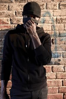 レンガの壁のそばに立っているマスクのアフリカ系アメリカ人の男、黒い服のフーリガン。黒人の男は社会に危険をもたらし、暗い路地で犠牲者を待って犯罪を犯します。社会問題、犯罪の概念