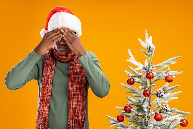 오렌지 배경 위에 크리스마스 트리 옆에 서있는 손으로 눈을 덮고 목 주위에 산타 모자와 스카프에 아프리카 계 미국인 남자