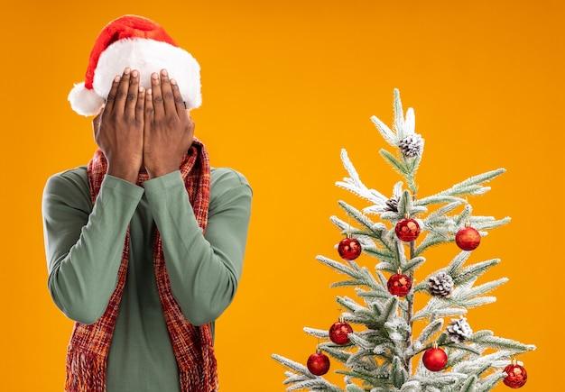 오렌지 벽 위에 크리스마스 트리 옆에 서있는 손으로 얼굴을 덮고 목 주위에 산타 모자와 스카프에 아프리카 계 미국인 남자