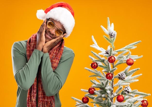 Афро-американский мужчина в новогодней шапке и шарфе на шее счастлив и позитивно стоит рядом с елкой над оранжевой стеной