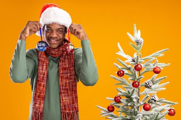 オレンジ色の背景の上のクリスマスツリーの横に幸せで前向きに立ってクリスマスボールを保持している首の周りのサンタの帽子とスカーフのアフリカ系アメリカ人の男