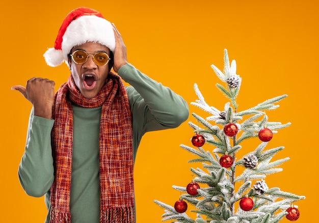 산타 모자와 스카프 목에 아프리카 계 미국인 남자는 오렌지 배경 위에 크리스마스 트리 옆에 서있는 측면을 엄지 손가락으로 가리키는 놀란 카메라를보고 놀랐습니다.
