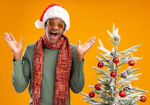 Афро-американский мужчина в новогодней шапке и шарфе на шее, глядя в камеру, счастливый и веселый стоит рядом с елкой на оранжевом фоне