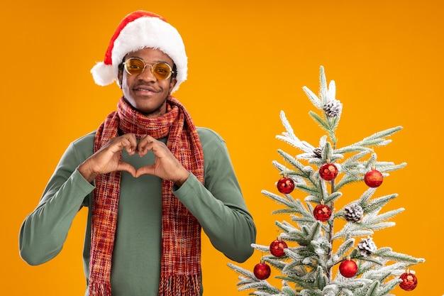 Афро-американский мужчина в новогодней шапке и шарфе на шее, делая жест сердца с пальцами, улыбаясь, стоит рядом с рождественской елкой на оранжевом фоне