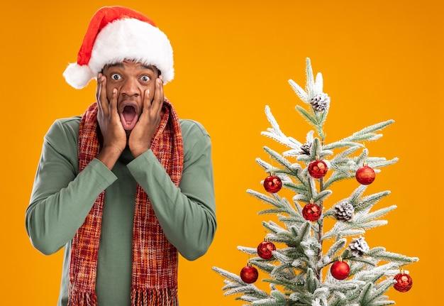 Афроамериканец в новогодней шапке и шарфе на шее в шоке стоит рядом с елкой над оранжевой стеной