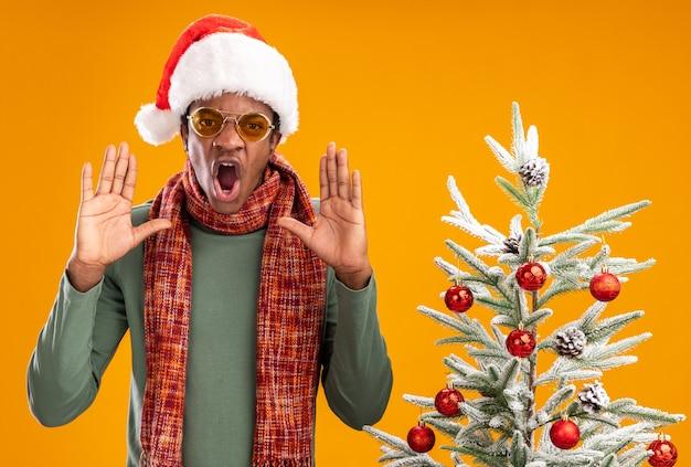 Афро-американский мужчина в новогодней шапке и шарфе на шее кричит с агрессивным выражением лица, стоя рядом с елкой над оранжевой стеной