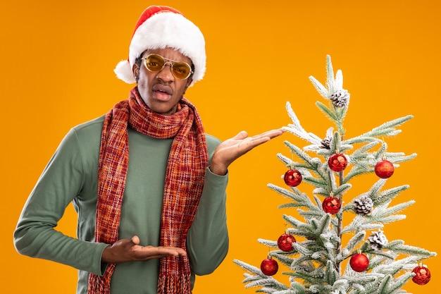 산타 모자와 스카프 목 주위에 아프리카 계 미국인 남자가 크리스마스 트리 옆에 서서 오렌지 벽에 혼란스럽고 불쾌한 표정으로 팔을 제시합니다.