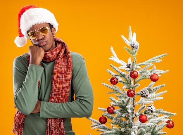 Афро-американский мужчина в шляпе санта-клауса и шарфе на шее с задумчивым выражением лица думает, стоя рядом с елкой над оранжевой стеной