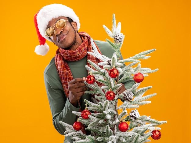 Афро-американский мужчина в новогодней шапке и шарфе на шее с улыбкой на лице стоит рядом с елкой над оранжевой стеной