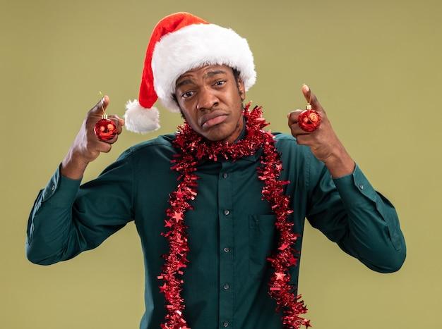 녹색 배경 위에 서있는 입술을 pursing 슬픈 표정으로 카메라를보고 크리스마스 공을 들고 갈 랜드와 산타 모자에 아프리카 계 미국인 남자