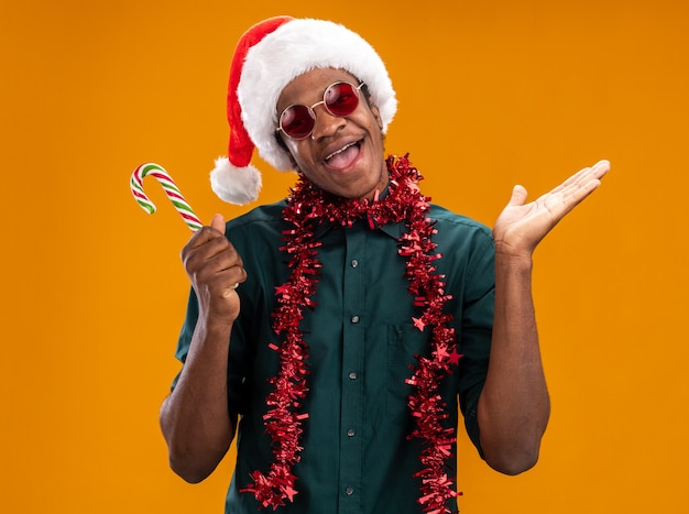 Афро-американский мужчина в шляпе санта-клауса с гирляндой в очках держит конфету счастливым и возбужденным, стоя над оранжевой стеной