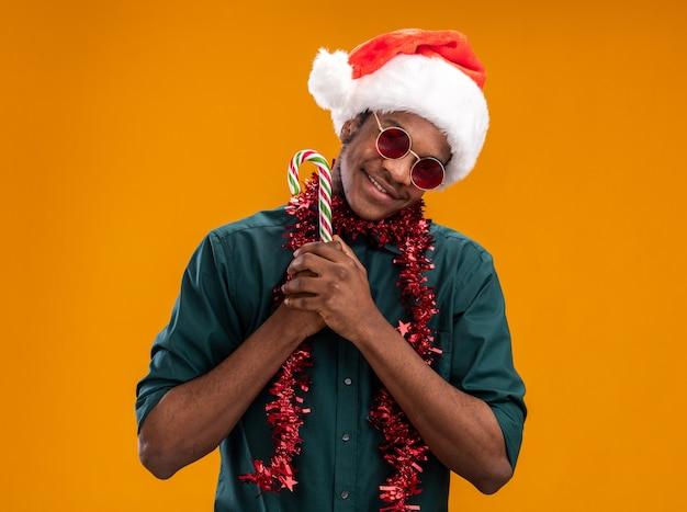 오렌지 배경 위에 서있는 얼굴에 미소로 카메라를보고 사탕 지팡이를 들고 안경을 쓰고 갈 랜드와 산타 모자에 아프리카 계 미국인 남자