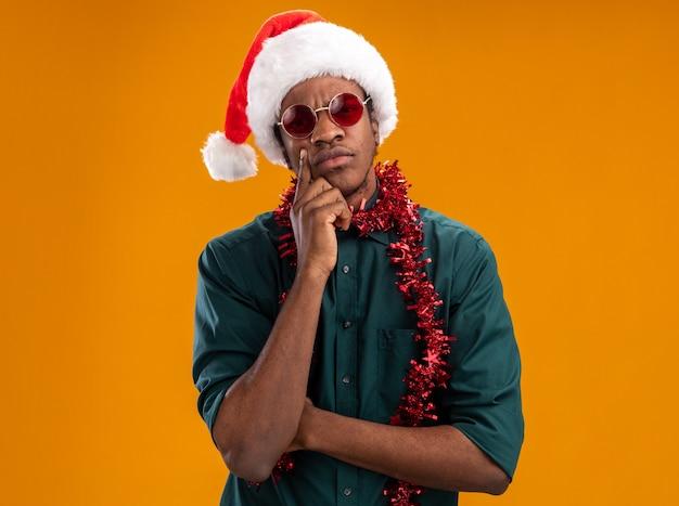 オレンジ色の壁の上に立って物思いにふける表現を考えてあごに手で眼鏡をかけて花輪とサンタの帽子をかぶったアフリカ系アメリカ人の男