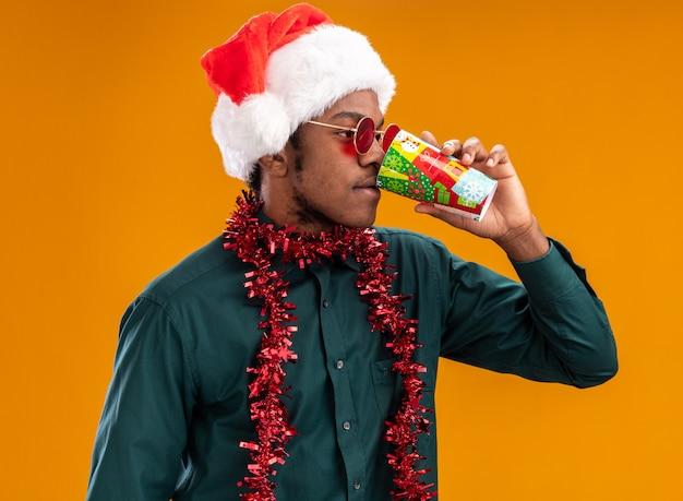 오렌지 벽 위에 서있는 다채로운 종이 컵에서 마시는 선글라스를 착용하는 갈 랜드와 산타 모자에 아프리카 계 미국인 남자