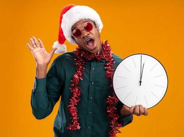 オレンジ色の背景の上に立っている腕を上げて驚いたカメラを見て時計を保持しているサングラスを身に着けている花輪とサンタ帽子のアフリカ系アメリカ人