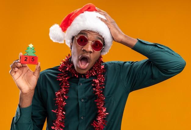 オレンジ色の背景の上に立って驚いて驚いたカメラを見て日付25のおもちゃの立方体を保持しているサングラスを身に着けている花輪とサンタの帽子をかぶったアフリカ系アメリカ人の男