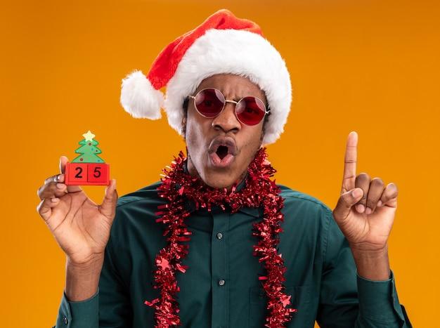 오렌지 벽 위에 서있는 검지 손가락을 보여주는 놀란 찾고 날짜 25와 장난감 큐브를 들고 선글라스를 착용하는 갈 랜드와 산타 모자에 아프리카 계 미국인 남자