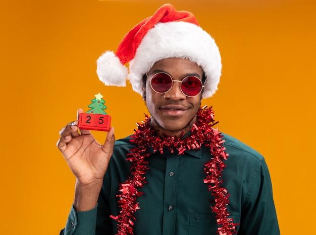 Афро-американский мужчина в шляпе санта-клауса с гирляндой в солнечных очках держит игрушечные кубики с датой двадцать пять, улыбаясь, стоя над оранжевой стеной