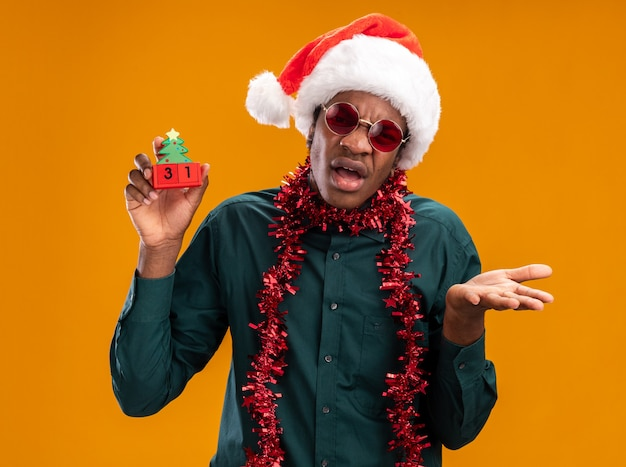 오렌지 배경 위에 서있는 팔과 혼동 카메라를보고 새 해 날짜와 장난감 큐브를 들고 선글라스를 착용하는 갈 랜드와 산타 모자에 아프리카 계 미국인 남자