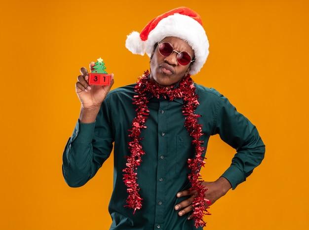 오렌지 배경 위에 서있는 얼굴을 찌푸리고 불쾌한 카메라를보고 새해 날짜와 장난감 큐브를 들고 선글라스를 착용하는 갈 랜드와 산타 모자에 아프리카 계 미국인 남자