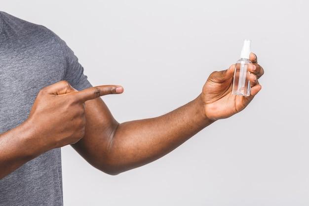 살 균 얼굴 마스크에 아프리카 계 미국인 남자입니다. 항균 소독제로 병을 들고 있습니다.